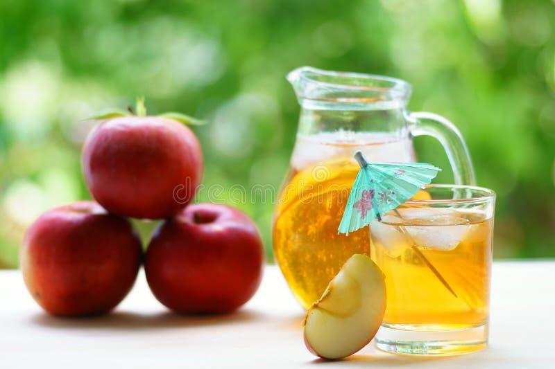 Succo di mele fresco con le mele rosse nel fondo fotografia stock