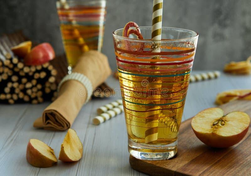 Succo di mele fresco in un vetro, paglia, mele rosse fotografia stock