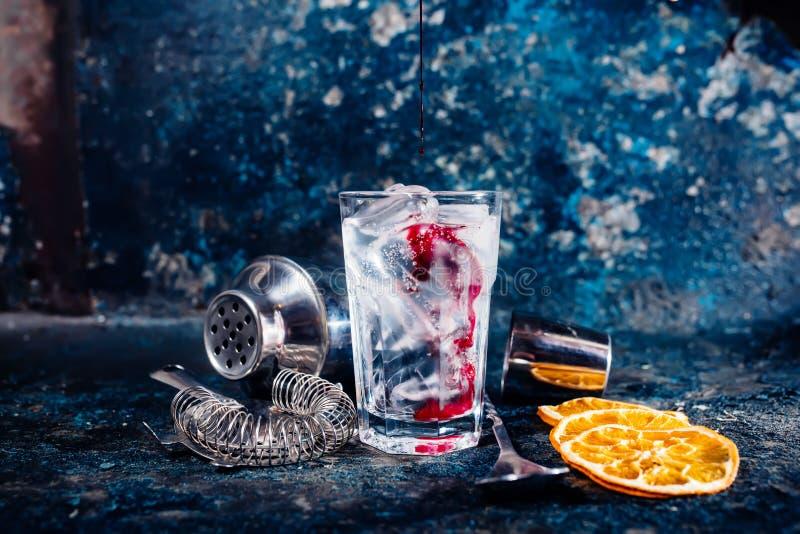 Succo di mirtillo rosso di versamento del barista sopra il cocktail della vodka immagine stock