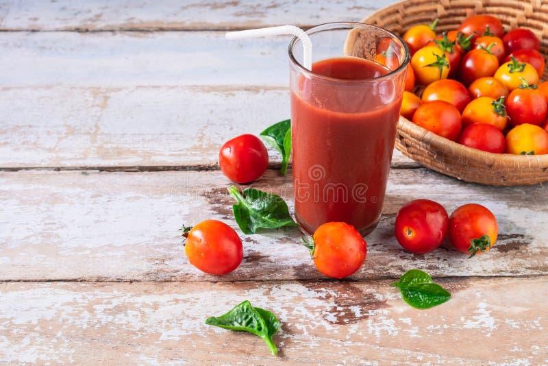 Succo di pomodoro fresco con i pomodori in un canestro fotografia stock