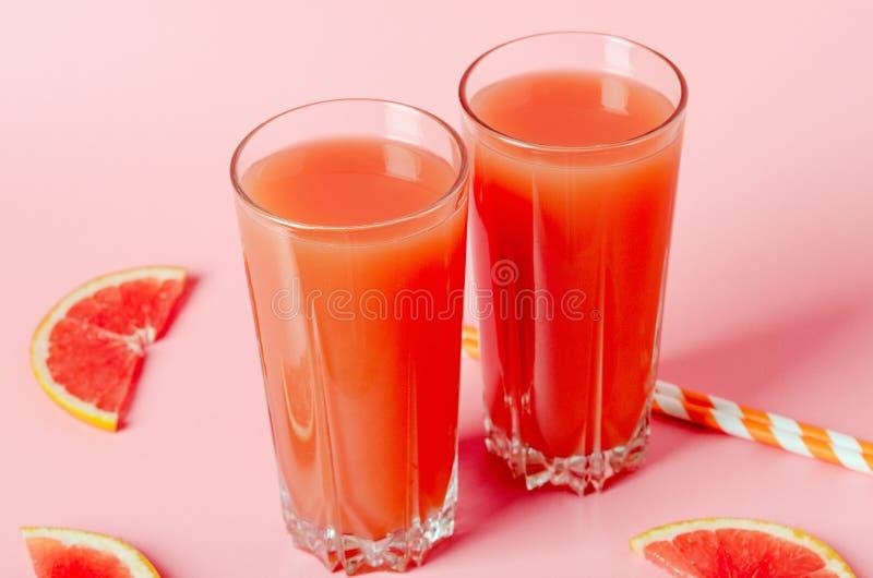 Succo di pompelmo di rinfresco con le paglie su un fondo rosa con le fette del pompelmo Bevanda di rinfresco di dieta di estate fotografia stock libera da diritti