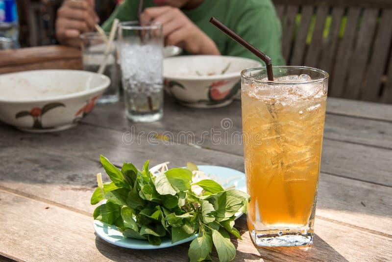 Succo di vetro del tamarindo con ghiaccio sulla tavola di legno immagini stock libere da diritti