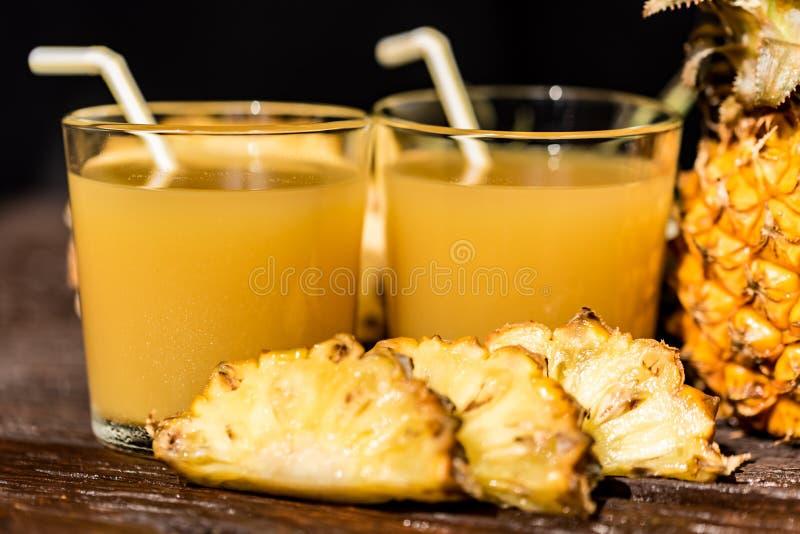 Succo e fetta di ananas disposti su una tavola di legno immagini stock libere da diritti