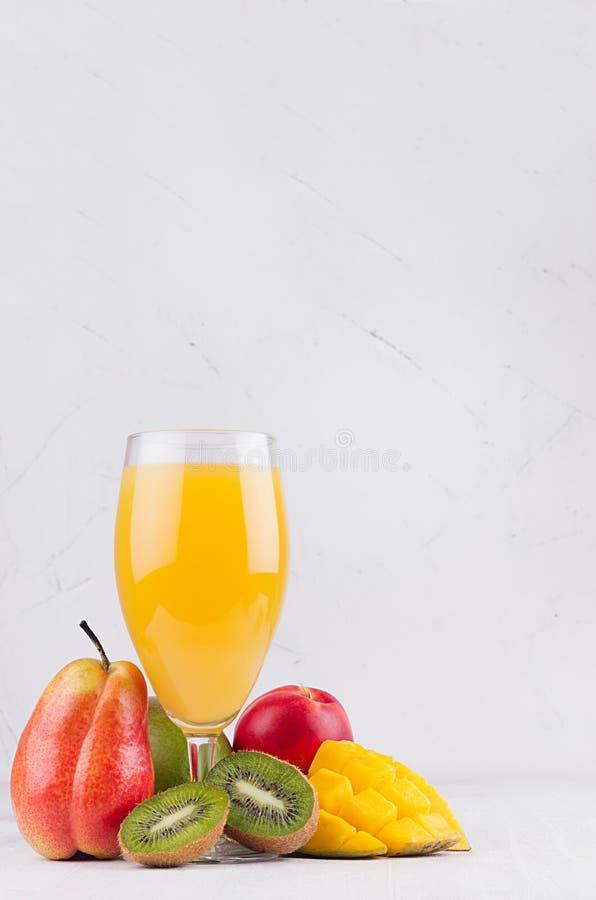Succo esotico arancio dei frutti differenti - mango, kiwi, banana, pera, pesca - con gli ingredienti su fondo di legno bianco immagini stock