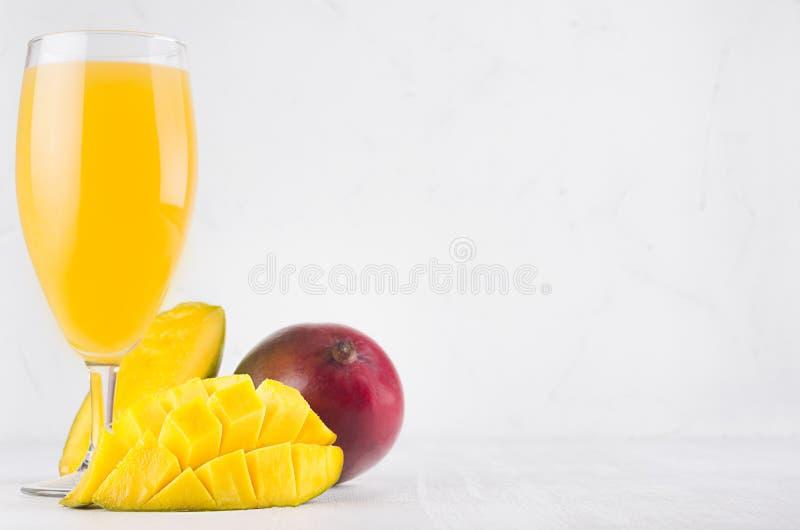 Succo giallo in vetro elegante con il mango maturo ed il mezzo primo piano affettato sul bordo di legno bianco Bevanda di frutta  immagini stock
