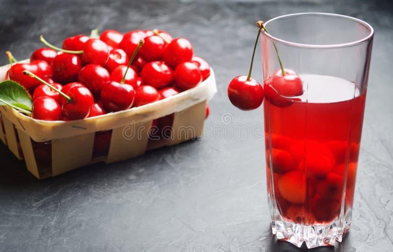 Succo o composta con le ciliege ciliegia rossa matura fresca in un canestro su un fondo concreto grigio, bacca di estate, bevanda immagini stock libere da diritti