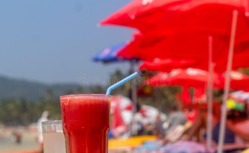 Succo rosso dell'anguria sulla spiaggia con le baracche ed il fondo dell'ombrello fotografie stock