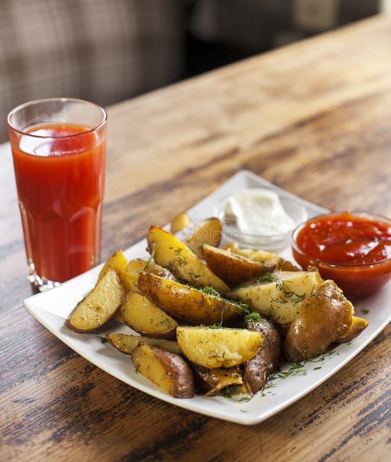 Succo saporito di pomodoro e di Fried Potato su una tavola immagine stock