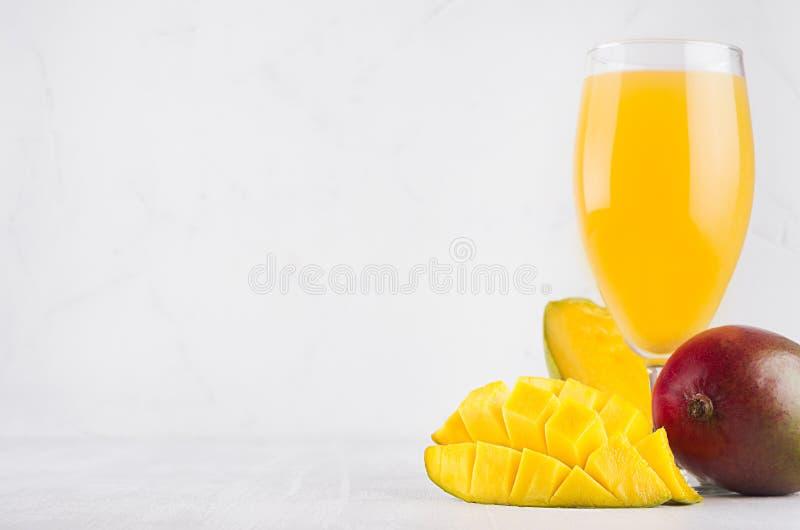 Succo tropicale di estate del mango fresco maturo con la fetta tagliata polposa sul fondo bianco elegante della luce morbida immagini stock