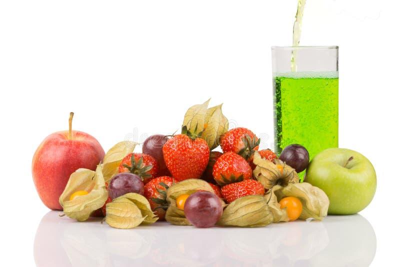 Succo verde che versa dentro alle mele rosse e verdi di vetro di behide con il physalis arancio, l'uva porpora e le fragole rosse immagini stock libere da diritti
