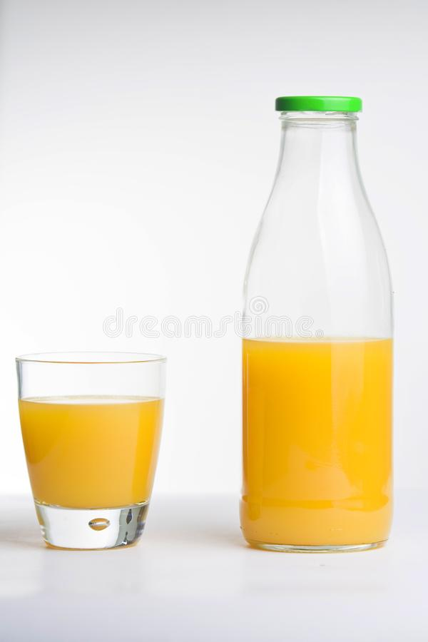Succo d'arancia, vetro e bottiglia fotografia stock libera da diritti