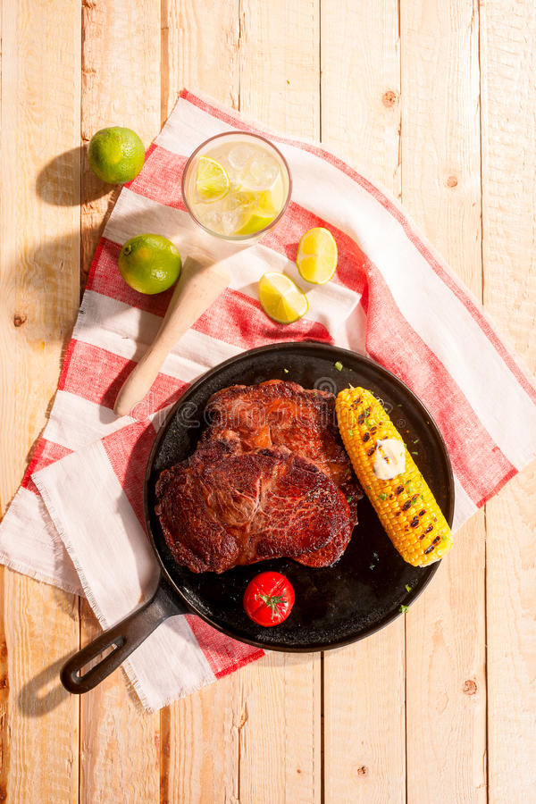 Succulent grilled beef steak with corn. On the cob served on a skillet with a chilled cocktail with lime garnish, overhead view on a wood table outdoors stock image