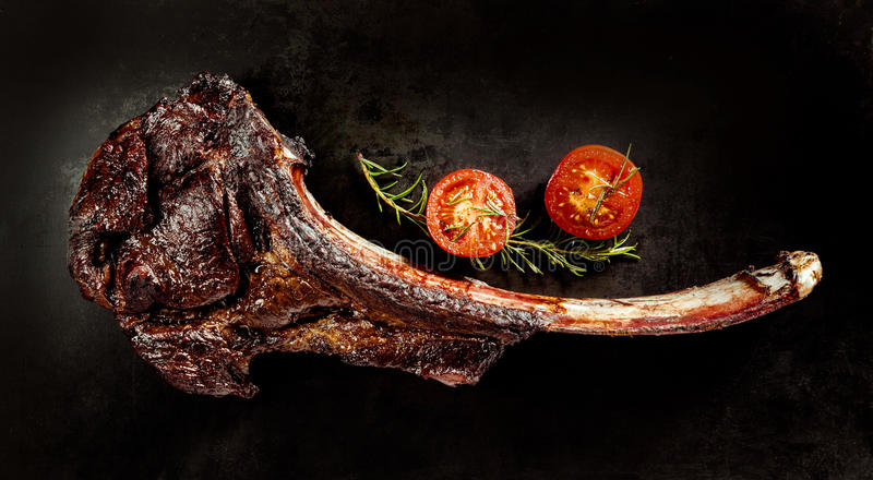 Succulent grilled tomahawk beef steak. On the bone with fresh rosemary and a cherry tomato on a black background viewed from above stock images