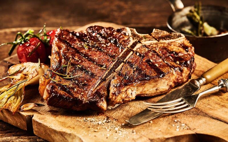 Succulent grillte Steak des förmigen Knochens mit Gabel und Messer lizenzfreies stockbild