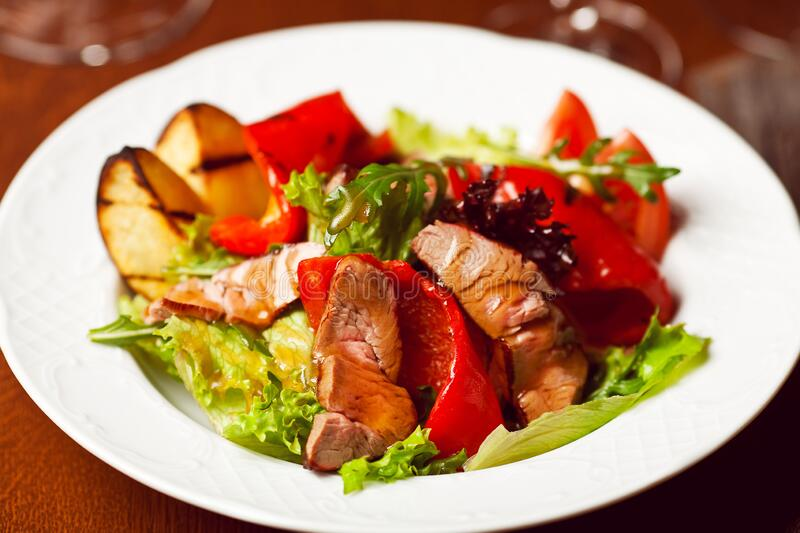 Succulent juicy portion of hot salad with grilled fillet steaks served with tomatoes, ruccola and roast vegetables on white plate stock photo