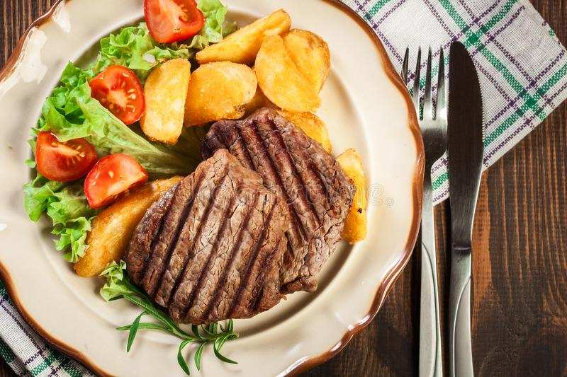 Succulent portions of grilled fillet mignon served with baked po. Tatoes on a plate. Top view stock photos