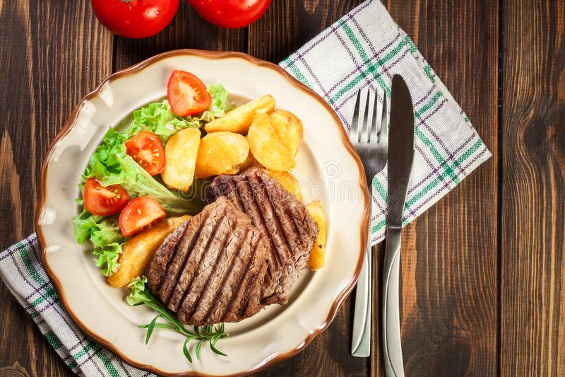 Succulent portions of grilled fillet mignon served with baked po. Tatoes on a plate. Top view royalty free stock photography