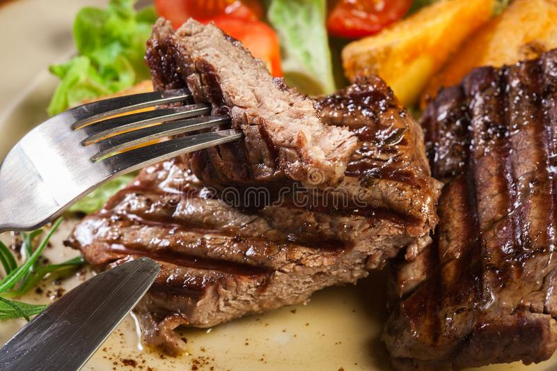 Succulent portions of grilled fillet mignon served with baked potatoes stock photo