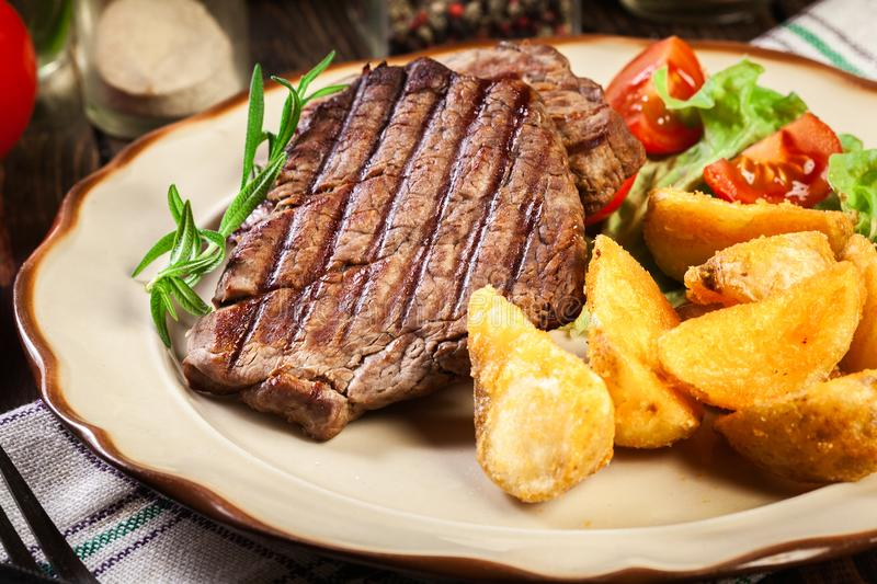 Succulent portions of grilled fillet mignon served with baked potatoes. On a plate stock images
