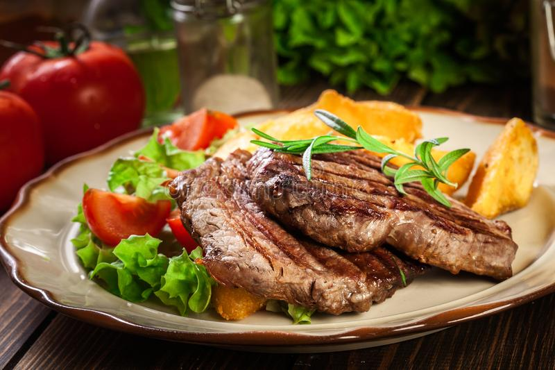Succulent portions of grilled fillet mignon served with baked potatoes. On a plate royalty free stock photos
