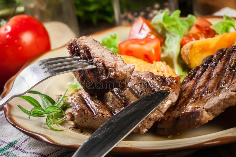 Succulent portions of grilled fillet mignon served with baked potatoes. On a plate royalty free stock photography