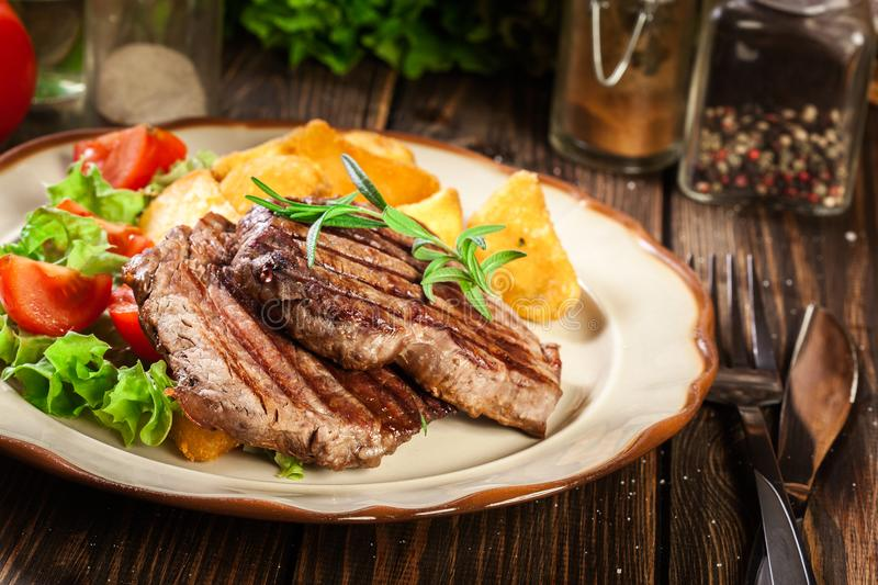 Succulent portions of grilled fillet mignon served with baked potatoes. On a plate stock photo