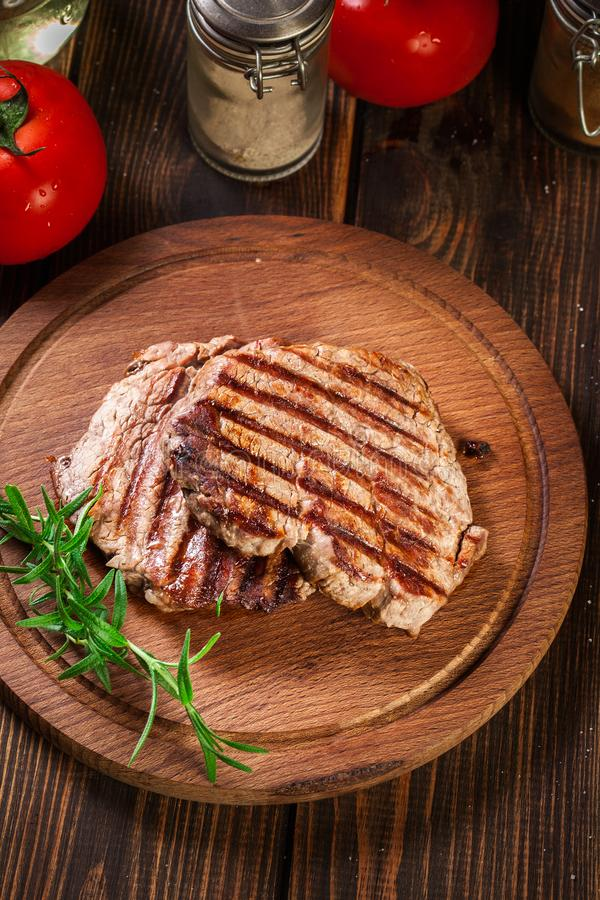 Succulent portions of grilled fillet mignon served with rosemary. On an wooden board. Top view stock photography