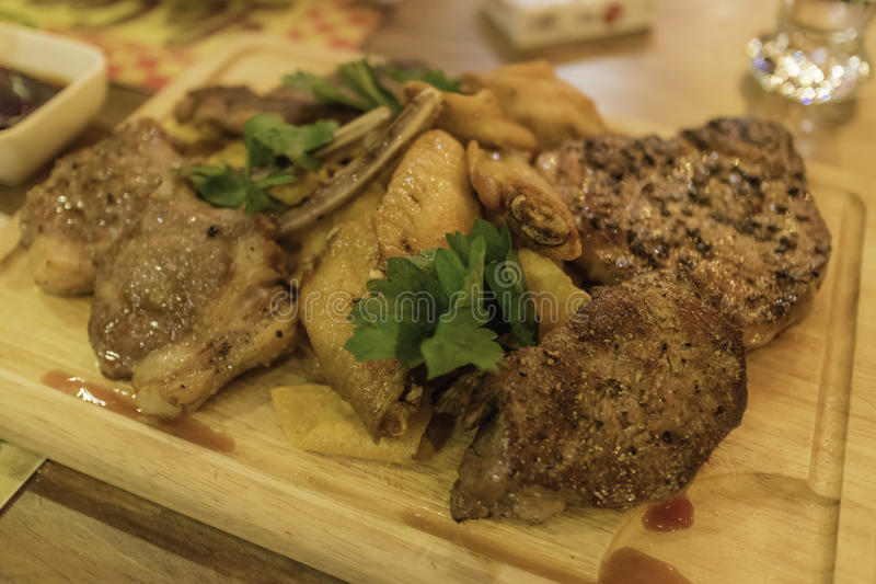 Succulent thick juicy portions and lamb chops, chicken wings of. Grilled steak on an wooden board royalty free stock photo