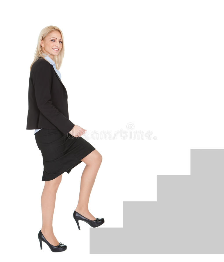 Sucessful businesswoman walking up a staircase royalty free stock photos