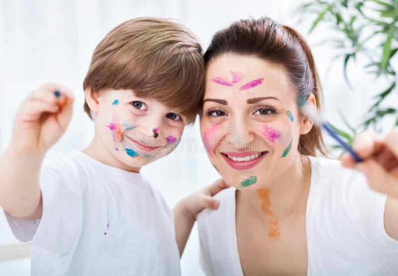 Sucesso atrativo adorável da pintura da mãe e da criança fotografia de stock