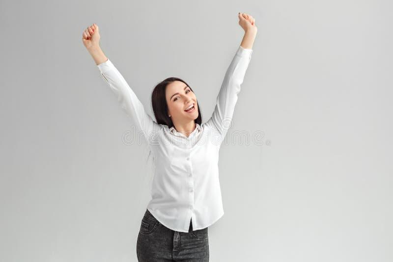 Sucesso conseguido Posição da mulher isolada nas mãos cinzentas acima da gritaria alegre fotos de stock royalty free