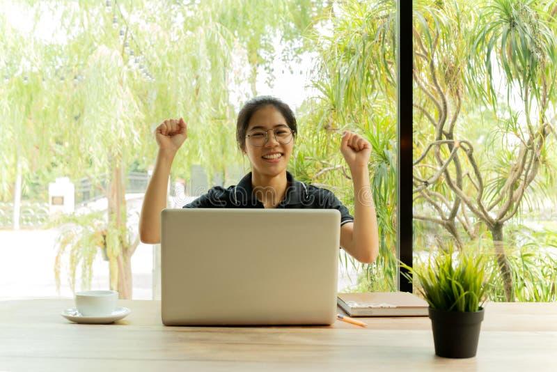 Sucesso de comemoração excitado alegre do adolescente asiático na frente do netbook fotografia de stock