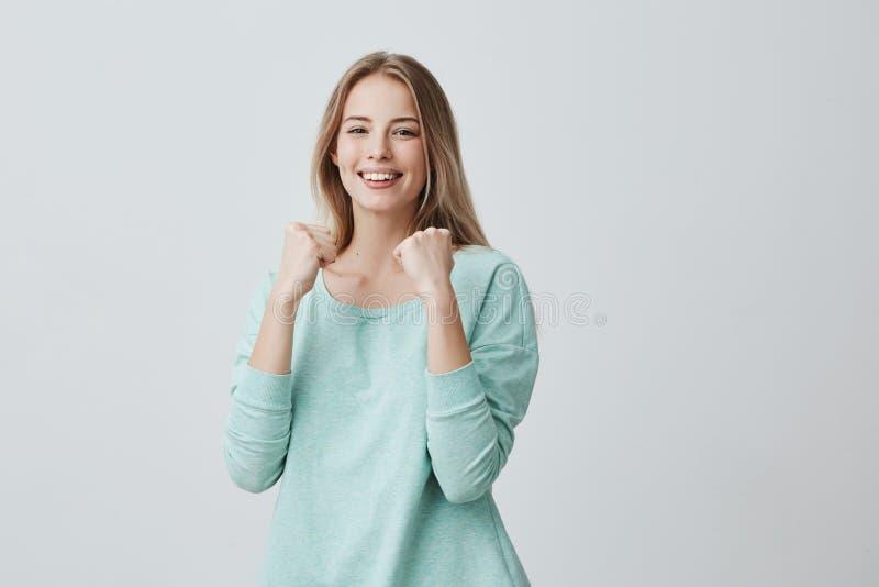 Sucesso fêmea novo afortunado do júbilo do empregado no trabalho, sorrindo amplamente, mantendo os punhos apertados menina loura  imagens de stock royalty free