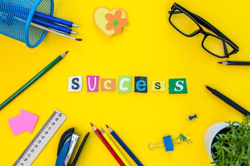 Sucesso - texto de letras cinzeladas no fundo amarelo da tabela com fontes do escritório ou do aluno Conceito para o sucesso foto de stock