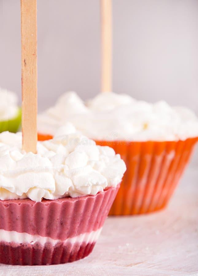 Sucettes de glace à l'eau de crème glacée de fraise avec la crème fouettée congelée dans des moules de petit pain sur le fond gri images stock