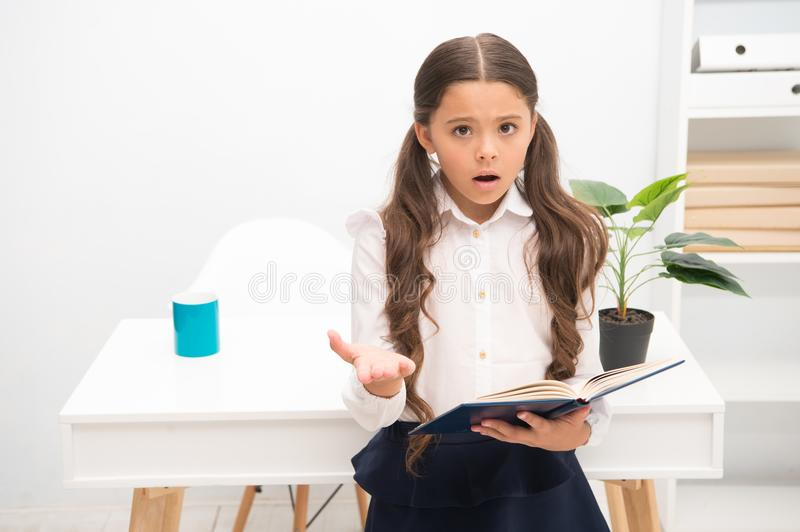 Such difficult topic. Studying difficulties. Girl read book while stand table white interior. Schoolgirl studying royalty free stock photos