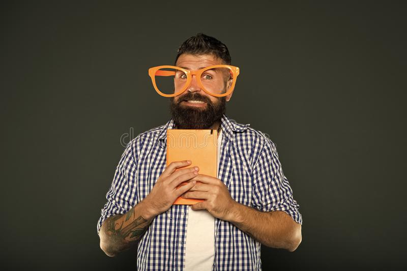 He is such a geek. University male student with lecture notes. Bearded man in party glasses with lesson book. Book nerd royalty free stock image