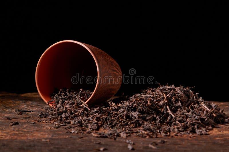 Sucha herbata w glinianej filiżance na drewnianym stole Selekcyjna ostrość, zamyka up fotografia stock