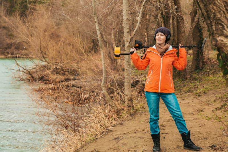 Suche mit einem Metalldetektor Eine junge Frau, die mit einem Metalldetektor auf der Flussbank aufwirft stockfotografie