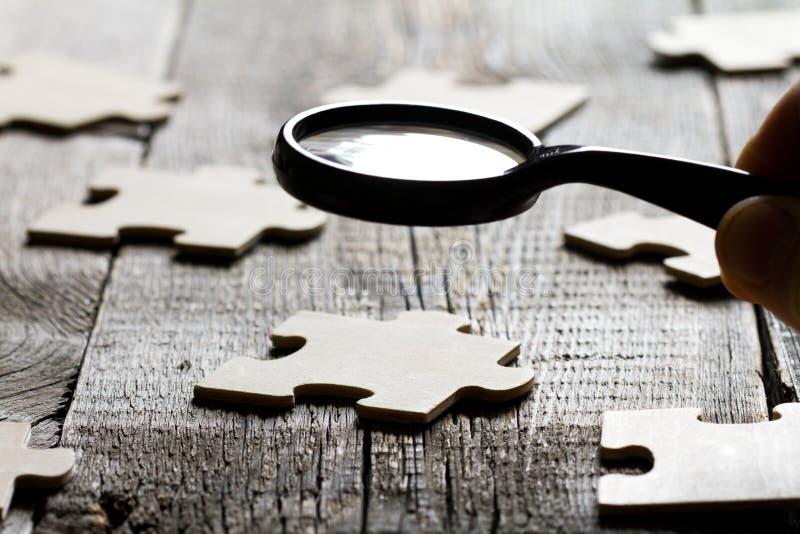 Suchen eines Angestelltpartners im Geschäftskonzept mit Puzzlespiel und Vergrößerungsglas stockfoto