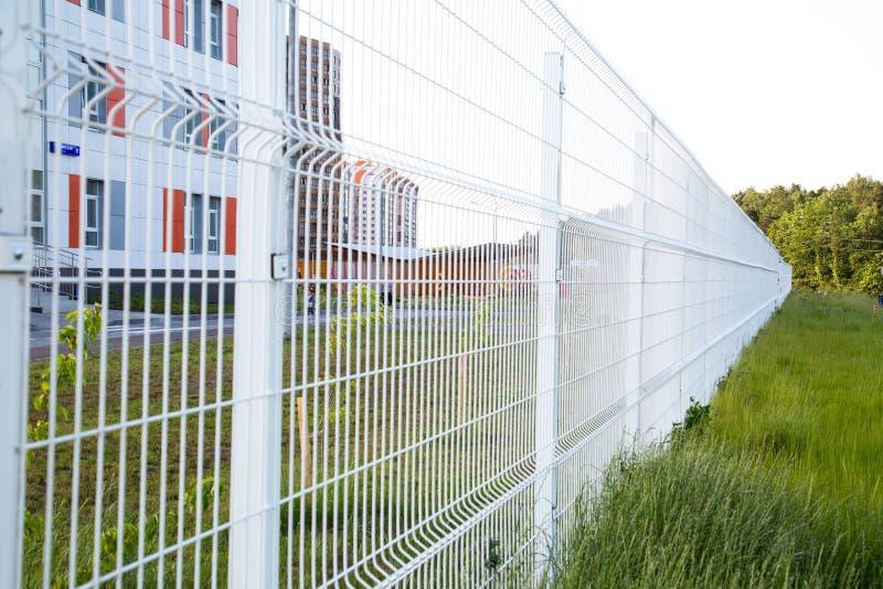 Suchen Sie nach weißem Gitterzaun in der Zukunft Selektiver Fokus stockfotografie