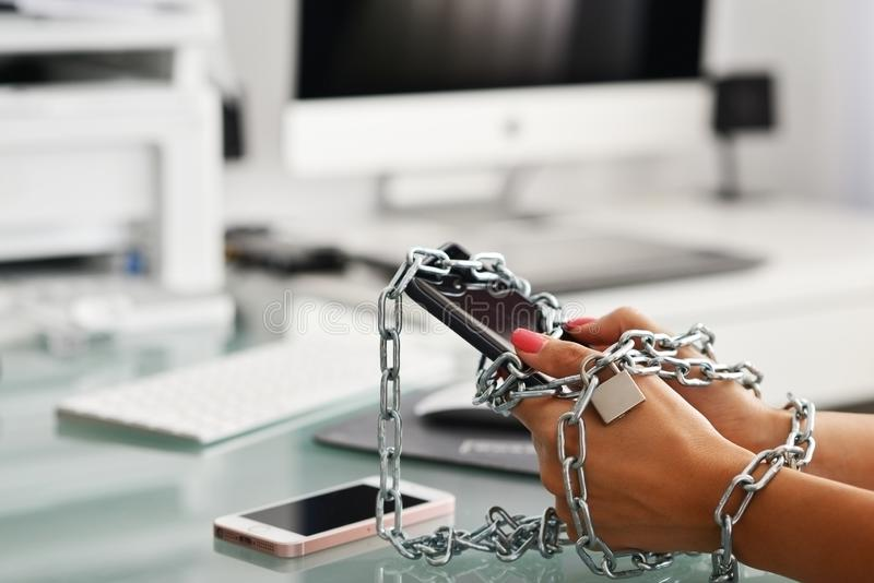 Sucht zum Smartphone- oder Gerätenkonzept mit woman's Händen band metallische Kette des Esprits unter Verwendung des Handys stockfotos