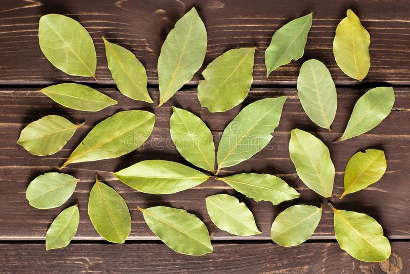 Suchy oliwny zielona zatoka bobek opuszcza na brown drewnie zdjęcie stock