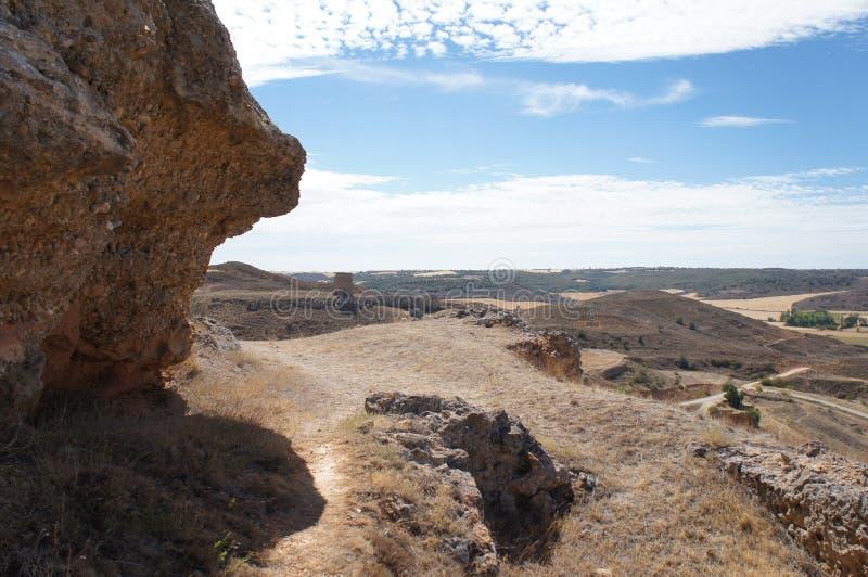 Suchy pole w Hiszpańskiej wiosce, sucha trawa, kamienie, kolor żółty, niebieskie niebo z białymi chmurami obraz stock