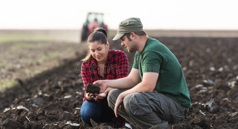 Suciedad joven del examen de los granjeros mientras que el tractor está arando el campo fotos de archivo libres de regalías
