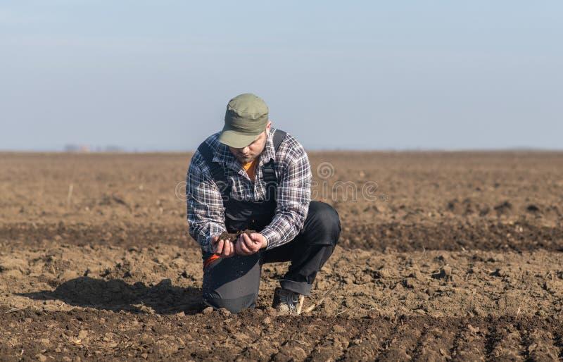 Suciedad joven del granjero mientras que el tractor está arando el campo fotografía de archivo libre de regalías