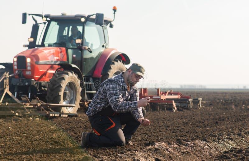 Suciedad joven del granjero mientras que el tractor está arando el campo foto de archivo libre de regalías