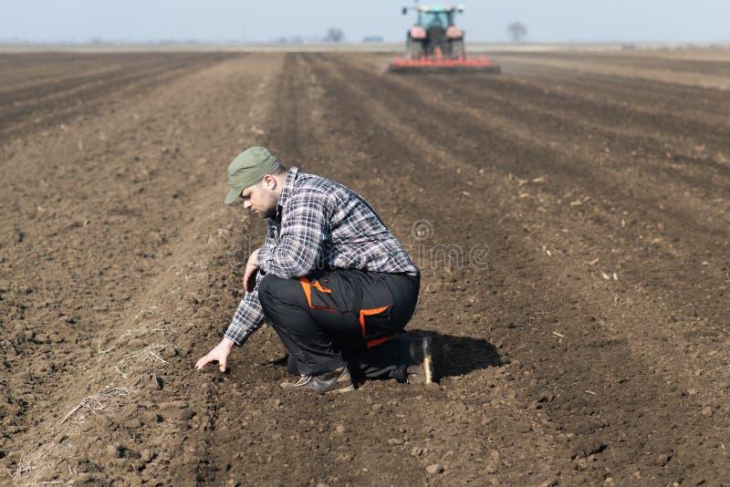 Suciedad joven del granjero mientras que el tractor está arando el campo fotos de archivo