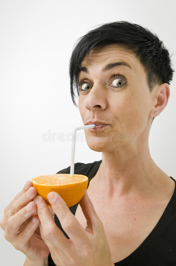 Suck at the straw. Head-and-shoulder shot pf black-haired middle-aged woman against white Background, drinking straw directly from halfed orange and smile into royalty free stock image