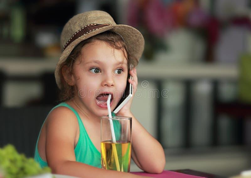 Suco bebendo da menina bonito surpreendente no café e discurso no mobi imagens de stock royalty free